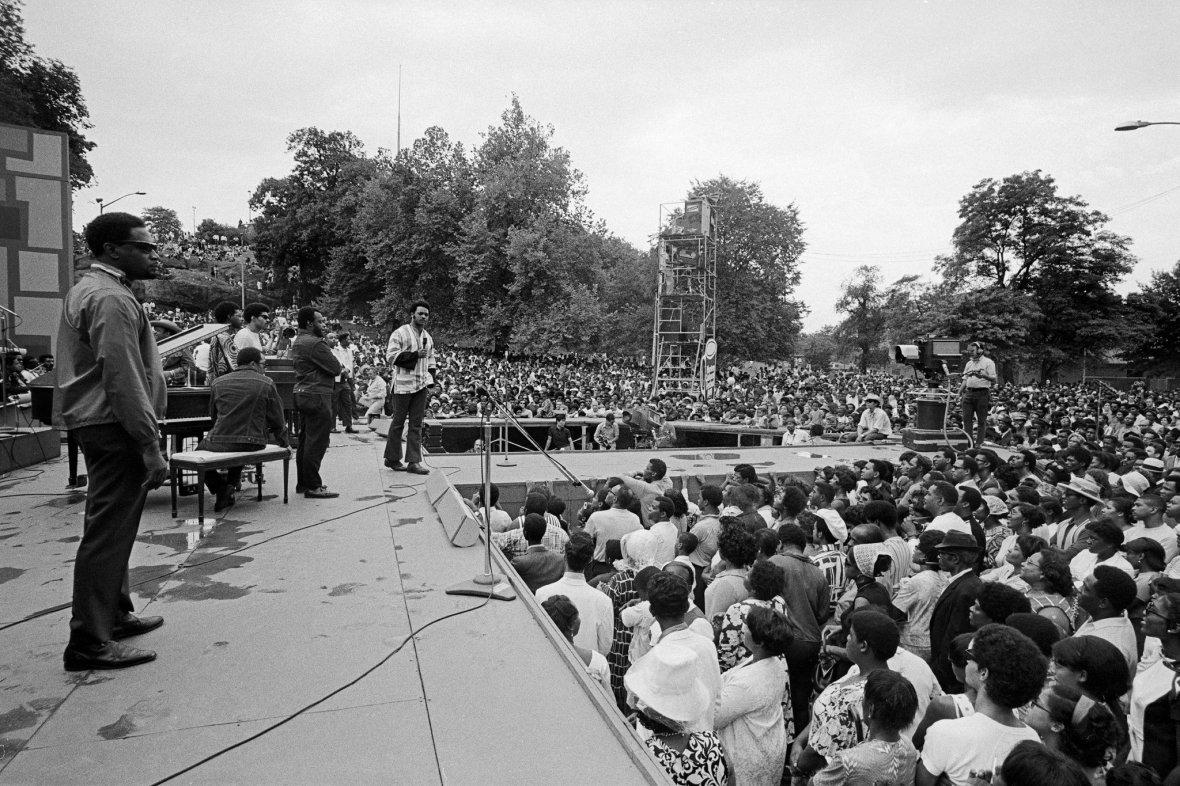 Jesse Jackson hablando a la multitud con la Operation Breadbasket Band detrás. Foto Donal F. Holway.jpg