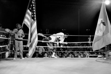 ZAIRE. Kinshasa. ALI-FOREMAN Boxing Fight. Muhammad ALI climbs on the ring between the American and the Zairian flags displayed before the fight. 1974.