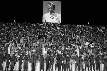 ZAIRE. Kinshasa. World Heavyweight Boxing Championship. At the stadium spectators stand underneath a portrait of Zaire's President MOBUTU. 1974.