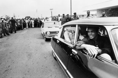 Former world heavyweight champion Muhammad Ali passes by a cheering crowd in Kinshasa, Zaire, on September 28, 1974 before his world heavyweight championship fight against champion in title George Foreman on October 30, 1974. Ali won by knocking out Foreman in the eighth round. (Photo credit should read -/AFP/Getty Images)