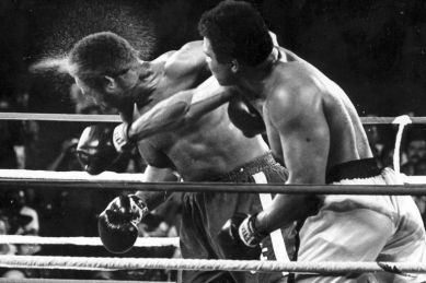 """FILE - In this Oct. 30, 1974, file photo, perspiration flies from the head of defending champion George Foreman as he takes a right from challenger Muhammad Ali in the seventh round in their world heavyweight championship bout dubbed """"Rumble in the Jungle"""" in Kinshasa, Zaire. Ali regained the world heavyweight crown by knocking out Foreman in the eighth round. (AP Photo/Ed Kolenovsky)"""